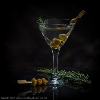 Vodka martini with olives and rosemary garnish