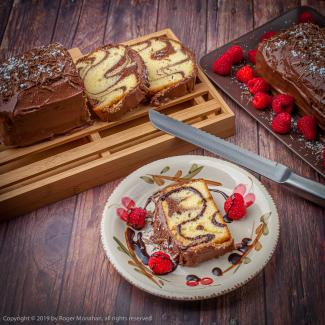 Marble Cake with chocolate icing sprinkled with icing sugar and served with raspberries